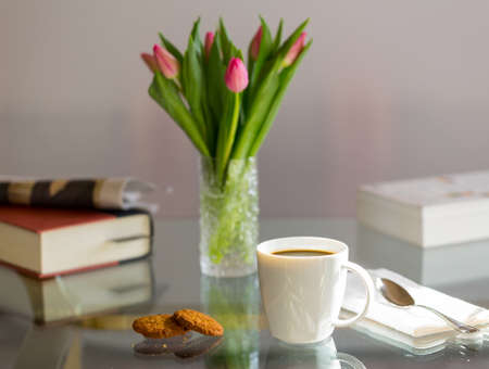 Modern white porcelain cup of black coffee on glass table with spoon and ginger biscuits photo