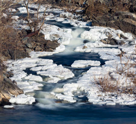 Great Falls on Potomac river outside Washington DC in winter with ice forming on the cascades and snow on the rocks Archivio Fotografico