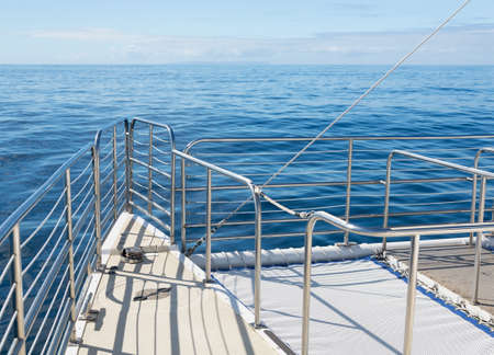 excursions: Large ocean going  catamaran at sea with focus on the stainless steel railings at the front of the boat