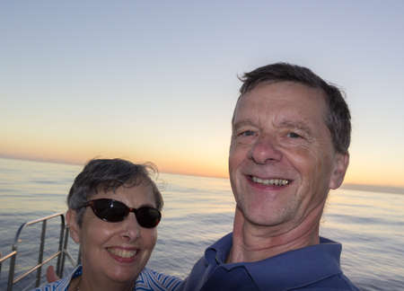 facing to camera: Selfie of middle aged couple on an ocean sunset cruise and leaning against the railings. Smiling and facing the camera.