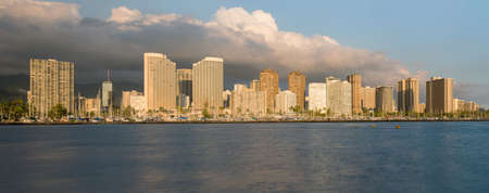 honolulu: Panorama of the skyline of Honolulu and Waikiki from Ala Moana park as the sun sets and illuminates the facades of the hotels and apartments
