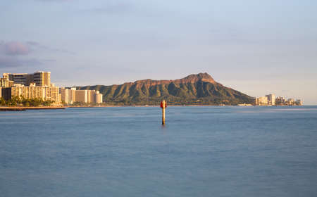 diamond head: Panorama of the skyline of Honolulu and Waikiki from Ala Moana park as the sun sets and illuminates the facades of the hotels and apartments