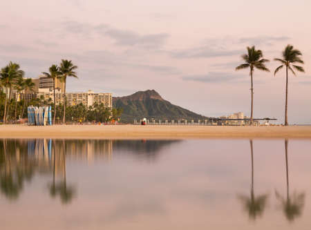 diamond head: Panorama of the skyline of Waikiki at dawn taken with a long exposure to blur out movement in the water and provide a reflection of Diamond Head in Hawaii