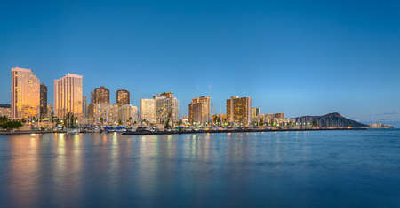 oahu: Panorama of the nightime skyline of Honolulu and Waikiki from Ala Moana park as the sun sets and illuminates the facades of the hotels and apartments