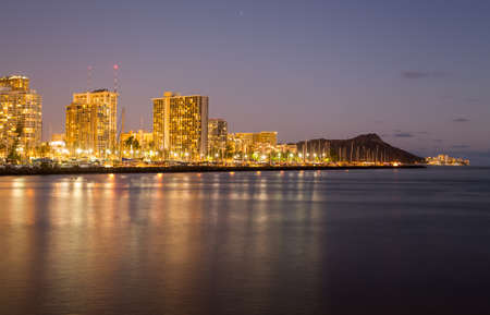 Panorama of the nightime skyline of Honolulu and Waikiki from Ala Moana park after the sun sets with lights illuminating the facades of the hotels and apartments photo