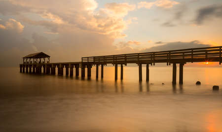 Long exposure image of Waimea pier at sunset blurs the ocean and bathes the structure in the warm glow of the setting sun.  photo