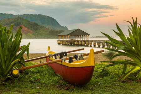 na: Red and yellow hawaiian canoe with outrigger on the beach at Hanalei pier at dawn as the sun lights the sky over Na Pali mountains