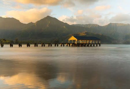 Rising sun illuminates the peaks of Na Pali mountains over the calm bay and Hanalei Pier photo