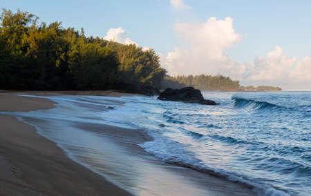 shorebreak: Rocks covered with surf and waves in ocean at Lumahai Beach in Kauai in Hawaiian islands Stock Photo