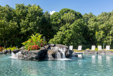 inground: Hot tropical swimming pool at resort with waterfall feature and reclining chairs on the patio with turquiose water