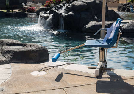 Chair lift for disabled person to enter resort swimming pool on hot sunny day with waterfall