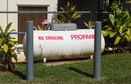 Large white propane storage tank behind protective pillars in landscaped garden by home or holiday resort
