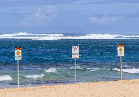 treacherous: Three warning sign no swimming and strong currents in treacherous winter waters on Tunnels Beach in Kauai Hawaii Stock Photo