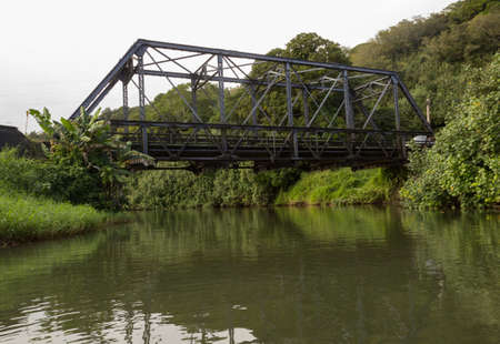 floating bridge: View of the old steel girder bridge over Hanalei river from a canoe floating down the wide stream under the road bridge