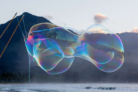 Man making multiple giant soap bubbles on Hanalei beach in Kauai Hawaii