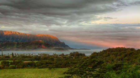 Bay at Hanalei in Kauai with the Na Pali mountain range in the background. Taken just after dawn with the rising sun skimming the peaks of the mountains and casting a sunbeam ray into the ocean photo