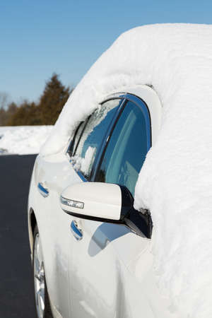 Deep snow piled high on top of white four door sedan car in rural setting with view down side of car and drive
