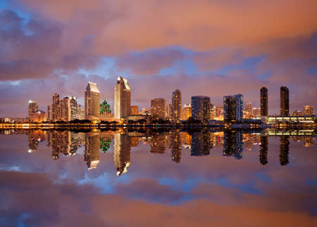 Skyline cityscape of San Diego downtown skyscrapers at night with lights reflecting into the ocean photo