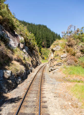 narrow gauge railroad: Railway track of Taieri Gorge tourist railway cuts through a narrow cutting in the rocks on its journey up the valley Stock Photo