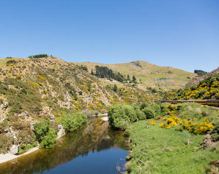 narrow gauge: Train and coaches of Taieri Gorge tourist railway runs alongside river in a ravine on its journey up the valley