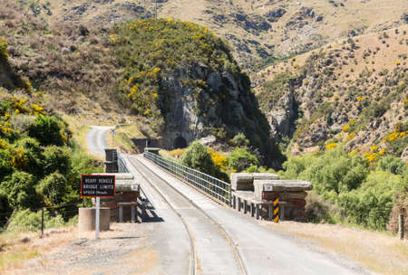 narrow gauge railways: Railway track of Taieri Gorge tourist railway shares a road bridge across a ravine on its journey up the valley