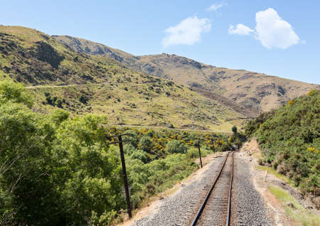 narrow gauge railways: Railway track of Taieri Gorge tourist railway passes zigzag road on its journey up the valley