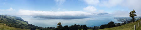 countryside landscape: Broad panoramic landscape of the Otago Peninsula and Bay with the city of Dunedin in the distance and clouds hanging over the mountains Stock Photo
