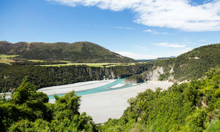 lowlands: View from the train windows of TranzAlpine railway over Waimakariri river gorge on journey to Arthurs Pass