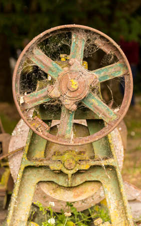 flywheel: Rusty farm equipment or machinery abandoned in forest with flywheel and motor pulley Stock Photo