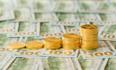 Stack of golden eagle coins in rising price graph or bar chart and standing on new design of US currency one hundred dollar bills photo