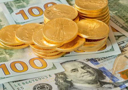 Stack of golden eagle coins on new design of US currency one hundred dollar bills with Benjamin Franklin portrait