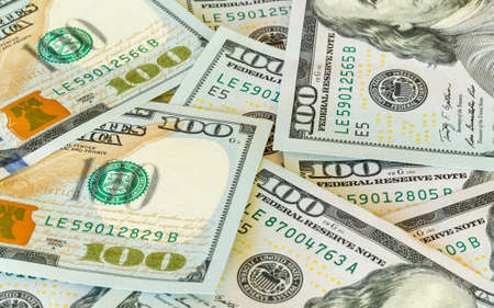 us currency: New design of US currency one hundred dollar bills laid out on table with focus on 100 numerals on back Stock Photo