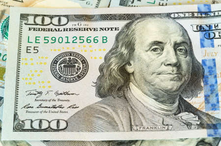 ben franklin: New design of US currency one hundred dollar bills laid out on table with focus on Ben Franklin portrait