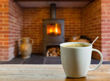 Coffee cup on wooden table in front of roaring fire inside wood burning stove in brick fireplace