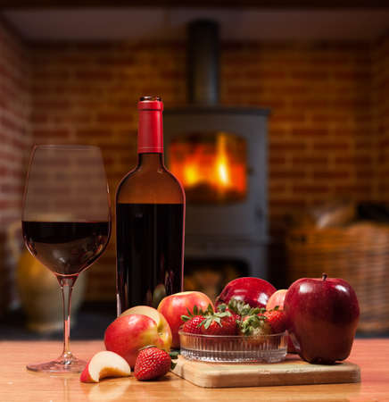 Red wine in bottle and glass with apple and strawberries on wooden table in front of roaring fire inside wood burning stove in brick fireplace photo