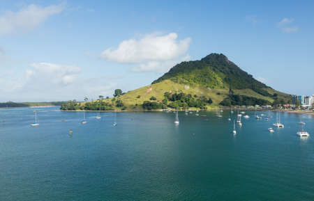 Bay and harbour at Tauranga with yachts and boats in the blue calm water in front of the Mount