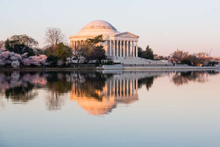 Sun rising illuminates the Jefferson Memorial and Tidal Basin with calm water of Tidal Basin reflecting the monument photo