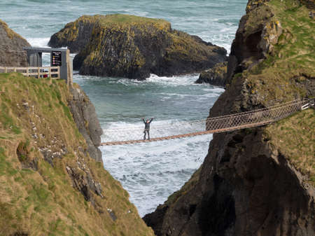 rope bridge: Young woman halfway across the Carrick a Rede rope suspension bridge to Carrick Island in Ulster or Northern Ireland County Antrim Stock Photo