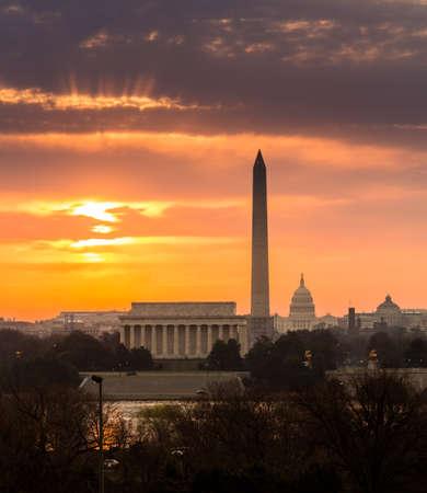 Bright orange sunlight illuminates clouds over Washington DC at dawn at sunrise. Lincoln, Washington Monument and Capitol are aligned photo