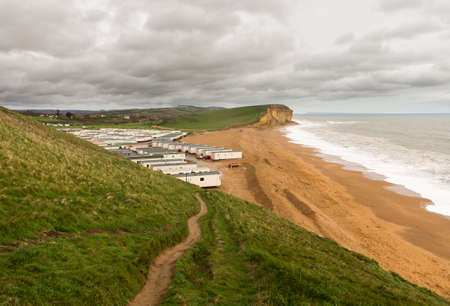 Mobile homes and caravans on beach by cliffs and headland at West Bay in Dorset used as the location for the Broadchurch TV series