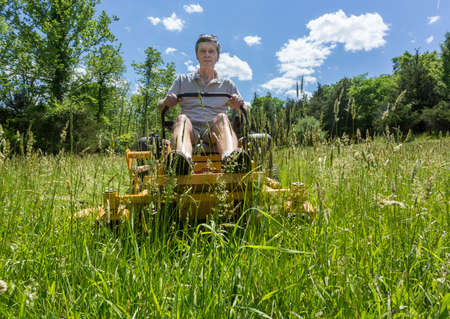 Senior retired male cutting very deep grass in a meadow or field after leaving it to grow for far too long before cutting using yellow zero-turn lawn mower Stock Photo