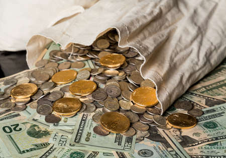 Thousands of US dollars  in notes and gold and silver coins pouring out of a cloth money bag  Stock Photo