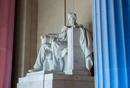 Red and blue pillars illuminate the white statue of President Lincoln in Lincoln Memorial in Washington DC in illustration of US flag