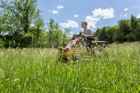 Senior retired male cutting very deep grass in a meadow or field after leaving it to grow for far too long before cutting. He is mowing sideways to the camera using yellow zero-turn lawn mower photo