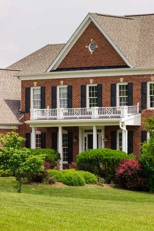 warm house: Vertical front of large single family modern US house with landscaped gardens and lawn on a warm sunny summers day Stock Photo