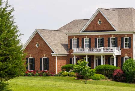 日当たりの良い夏の日、大規模な単一家族現代米国家の暖かく芝生と美しい庭園の正面図