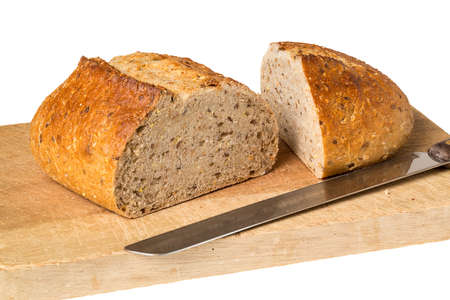 Whole wheat or multi grain brown bread fresh from oven bakery placed on wooden breadboard with knife and isolated  photo