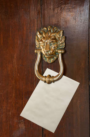 old envelope: Envelope with space for text placed under a brass lion head door knocker on old oak door