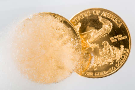 ounce: Gold eagle one ounce coin emerging from a frozen ice block to illustrate concept of gold coming out of deep freeze and price going to rise Stock Photo