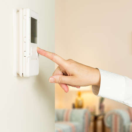 Caucasian female hand pressing button on a modern electronic thermostat timer on wall of a modern home with focus on the screen and fingers of the woman photo